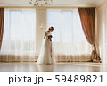 Bride standing alone with bridal bouquet near a big window 59489821