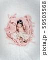 Portrait of newborn baby boy lying in a basket with silver crown. 59503568