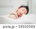 Newborn baby boy sleeping and wearing a silver crown. 59503569