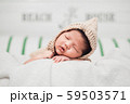 Happy cute adorable Asian baby boy with black hair lying on a white blanket. 59503571