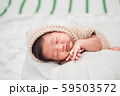 Adorable newborn baby peacefully sleeping on a white blanket. 59503572