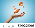 Closeup of woman's hand levitating two orange safety cones on light blue background. 59922596