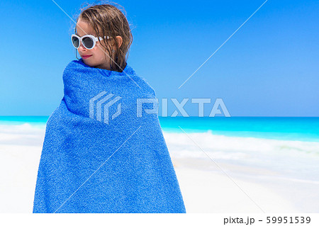 Adorable little girl wrapped in towel at tropical beach after swimming in the sea 59951539