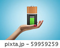 Female hand holding fully charged battery on blue background 59959259
