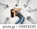 Young girl bending down covering her face with her hands trying to protect herself from mens' fists, finger guns and hands pointing at her. 59959293