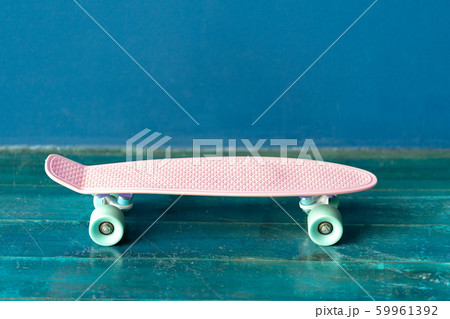 Pink skateboard on the wooden floor against blue wall 59961392