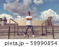 Male athlete, summer city, stands pose dancer, hip hop style, break dancer. Building staircase background. Active youth lifestyle, modern fashionable hipster, street dancer. Sneakers jeans sunglasses. 59990854
