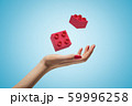 Female hand throwing two red toy blocks up in the air on blue background 59996258