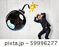 Young businessman protecting his head with his hands and big cartoon ball bomb on white background 59996277