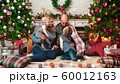 Happy successful family sits in the Christmas setting in the living room 60012163