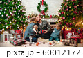 Christmas concept - happy successful family sits in the Christmas setting and exchange gifts - mom 60012172