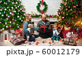 Christmas concept - happy successful family sits in the Christmas setting and holding gifts 60012179