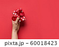 Woman hands holding red giftbox with red bow . 60018423