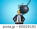 Businessman wearing yellow safety helmet and metal chained ball breaking into pieces on blue background 60029192