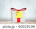 3d close-up rendering of white gift box with yellow post-it note on, saying 'From' and 'To', standing on wooden surface. 60029196
