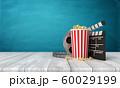 3d rendering of pop corn bucket, film reel, and clapperboard standing on wooden floor near blue wall. 60029199