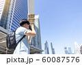 Young traveler looking at viewfinder of camera 60087576