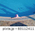 Young woman sunbathing in a swimming pool 60112411