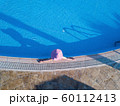 Young woman sunbathing in a swimming pool 60112413