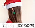 Closeup portrait of a girl an earring shape of a Christmas green ball 60156275