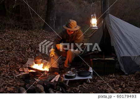 ソロキャンプ 焚火をする男性 60179493