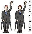 椅子に座り手を挙げる男性 60180126
