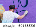 Graffiti artist painting with aerosol spray bottle 60183556