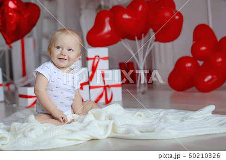 Boy on birthday party 1 year on the background of red balloons 60210326