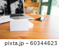 Blank business cards and laptop on wooden surface 60344623