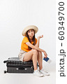 Lifestyle and travel Concept: Young beautiful caucasian woman is sitting on suitecase and waiting for her flight.Isolated over white background 60349700