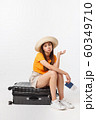 Lifestyle and travel Concept: Young beautiful caucasian woman is sitting on suitecase and waiting for her flight.Isolated over white background 60349710