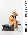 Lifestyle and travel Concept: Young beautiful caucasian woman is sitting on suitecase and waiting for her flight.Isolated over white background 60349713