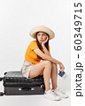 Lifestyle and travel Concept: Young beautiful caucasian woman is sitting on suitecase and waiting for her flight.Isolated over white background 60349715