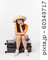 Lifestyle and travel Concept: Young beautiful caucasian woman is sitting on suitecase and waiting for her flight.Isolated over white background 60349717