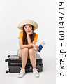 Lifestyle and travel Concept: Young beautiful caucasian woman is sitting on suitecase and waiting for her flight.Isolated over white background 60349719