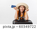 Travel concept. Studio portrait of pretty young woman holding passport and luggage. Isolated on white 60349722