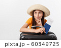 Travel concept. Studio portrait of pretty young woman holding passport and luggage. Isolated on white 60349725