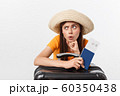 Lifestyle and travel Concept: Young beautiful caucasian woman is sitting on suitecase and waiting for her flight.Isolated over white background 60350438