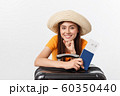 Travel concept. Studio portrait of pretty young woman holding passport and luggage. Isolated on white 60350440