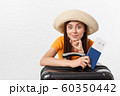 Travel concept. Studio portrait of pretty young woman holding passport and luggage. Isolated on white 60350442