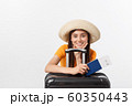Travel concept. Studio portrait of pretty young woman holding passport and luggage. Isolated on white 60350443