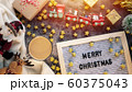 a cup of hot coffee in winter season with text Merry Christmas on letter board , Christmas ornament decorations and gift box on table for Christmas background 60375043