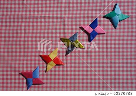 ギンガムチェックの布の上の折り紙の手裏剣 60570738