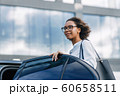 Young businesswoman getting into a taxi. Beautiful female standing at car outdoors. 60658511