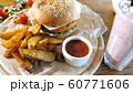 Crispy rustic potatoes with hamburger on wooden board. Fast food concept. 60771606