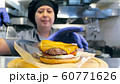 Female chef is preparing a delicious burger with cheese at restaurant kitchen 60771626