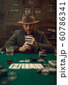 Poker player in suit and hat plays in casino 60786341