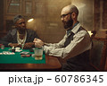 Poker players place money bets on gaming table 60786345