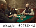 Three poker players with cards playing in casino 60786448