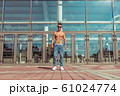 Young guy, athlete dancer, stands background of glass windows, trained happy smiling posing in summer in the city. Hip hop dancing. Jeans sunglasses. 61024774